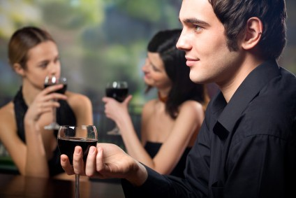 Young handsome man with glass of red-wine and two attractive wom